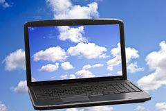 Cloud Computing Technology Concept. Laptop with a screen full of laptops in the clouds Royalty Free Stock Photos