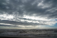 Cloud Cover. Dramatic clouds race over the New Zealand shore Stock Images