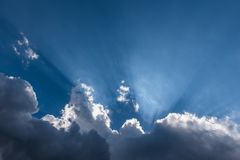 Cloud cover breaking to show heavenly sun beams royalty free stock photo