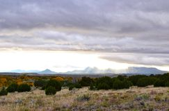 Cloud cover in galisteo new Mexico. Sun shining through thick clouds in Galisteo New Mexico during Indian summer in the fall, promising long awaited rain i after stock image