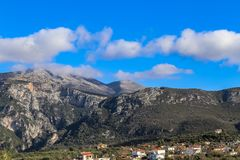 Cloud covered Taygetos mountains of the Peloponnese peninula of Southern Greece looking over the tile roofs of a village on a wint stock images
