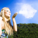 Cloud Creation With A Puff Of Magic. A beautiful blonde girl gently blows a puff of white dust into the blue sky in a creation concept Stock Image