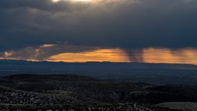 At sunset rain falls from clouds over the hills of a desert Royalty Free Stock Photography