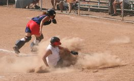 Cloud of Dust. A young lady, or teen, sliding into home plate and creating a cloud of shale dust Stock Image