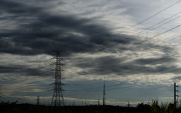 Cloud with electric tower. Electric tower with raining cloud and blue sky before sunset Stock Photography
