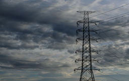 Cloud with electric tower. Electric tower with raining cloud and blue sky before sunset Royalty Free Stock Image