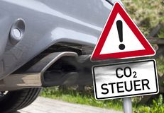 Cloud of exhaust with traffic sign and the german word for co2-tax - co2 Steuer. Cloud of exhaust with traffic sign or road sign and the german word for co2-tax royalty free stock image