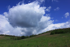 Cloud explosion. Dark clouds on a blue sky, green summer valley Royalty Free Stock Photography