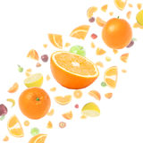 Cloud of flying fruits. Cloud of many flying fruits on white background with oranges in foreground royalty free stock photo
