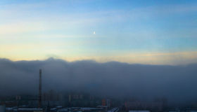 Cloud of fog and smog pollution covers the city from above a clear sky and the Moon Royalty Free Stock Photos