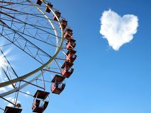 Cloud in the form of hearts and a Ferris wheel. On the blue clear sky Stock Photo