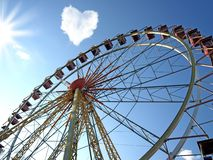 Cloud in the form of hearts and a Ferris wheel. On the blue sky Stock Photography