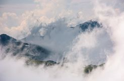 Cloud formation in mountains on high altitude. Spectacular natural phenomenon in summer. lovely weather background of hills with snow and grass Royalty Free Stock Photo