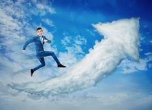 Cloud graph arrow. Surreal view as a happy businessman jump on a cloud graph arrow going up over a blue sky background. No limits success concept, business royalty free stock image