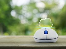 Cloud computing concept. Cloud icon with copy space and wireless computer mouse on wooden table over blur green tree in park, Cloud computing concept Royalty Free Stock Images