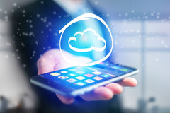 Cloud icon going out a smartphone interface of a businessman - b Stock Photo