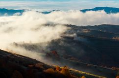 Cloud inversion in autumn mountains. Beautiful nature scenery. fog rolling above the rural fields in forenoon Stock Photography