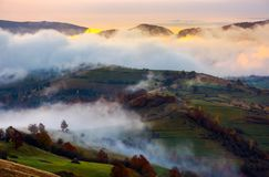 Cloud inversion in autumn mountains at dawn. Beautiful nature scenery. fog rolling above the rural fields Stock Image