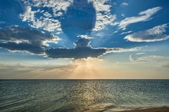 A cloud like a submarine flying on the sea, due to which the sun`s rays break through. At sunset stock photo