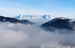 A cloud in the Low Tatras mountains and a view of the snowy peak Royalty Free Stock Photos