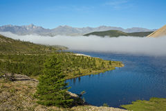 A cloud of mist over a mountain lake. Lake Darpir. Yakutia. Russia Royalty Free Stock Images
