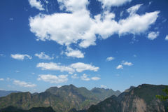 Cloud and mountain. White cloud in blue sky above mountains Royalty Free Stock Photo