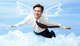 On cloud nine. Conceptual image of contented businessman with wings flying in the clouds Royalty Free Stock Photography