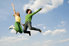 On cloud nine. Image of cheerful girl and guy jumping high against bright blue sky and laughing Stock Photos