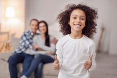 Inspired child showing her thumbs up. On cloud nine. Nice joyful curly-haired girl smiling and showing her thumbs up and her sitting on the couch in the Stock Images