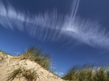 A cloud over a dune. A white cloud contrast with the blue sky over the dunes on a beautiful summer day Stock Photo
