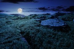 Cloud over the grassy hillside with rocks at night. In full moon light. path uphill in to the sky. lovely summer scenery. tracking and hiking activity Stock Image