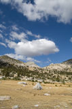 Cloud over high-land meadows. View across open grassy highland meadow with stones, granite hills and a large white cloud hanging overhead in Tolumne Meadows stock images