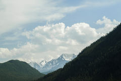 Cloud over the mountain range. Blue sky and green grass in a valley Royalty Free Stock Photography