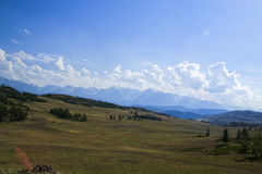 Cloud over the mountain range. Blue sky and green grass in a valley Royalty Free Stock Image