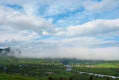 Cloud over the village. Morning fog. Giant cloud. Village in the Carpathians mountains. Stock Photos
