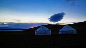 Cloud over the yurts at the shore of Song Kol Lake at dawn, Kyrgyzstan. Cloud over the yurts at the shore of Song Kol Lake at the dawn, Kyrgyzstan Stock Photos