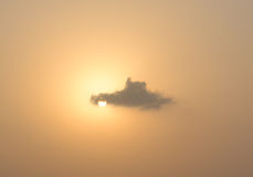 Cloud passing on the setting Sun. Cloud passing over the evening sunset in golden sky Royalty Free Stock Images