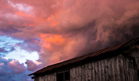 Cloud. Pink cloud descends upon the roof of the house Royalty Free Stock Image