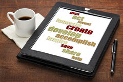 Cloud of positive words on digital tablet. Plan, act, create, share - cloud of positive energy and motivational words on a digital tablet with a cup of coffee royalty free stock image