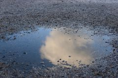 Cloud in puddle reflection gravel royalty free stock images