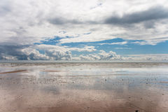 Cloud reflection in the wet sand after the storm. Empty beach with clouds reflected in the wet sand Royalty Free Stock Image