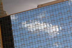 Cloud Reflection In Windows. Clouds in a blue sky are reflected in the windows of a building in a metropolitan area. The sky in the background is clouding over Stock Photography
