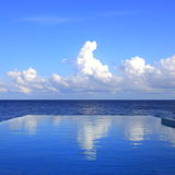 Cloud reflections on the infinity pool. Cloud reflections on the private infinity pool in a luxurious villa at Maldives Royalty Free Stock Images