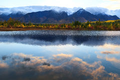Cloud reflections in smooth water surface, autumn forest and mou Stock Photos