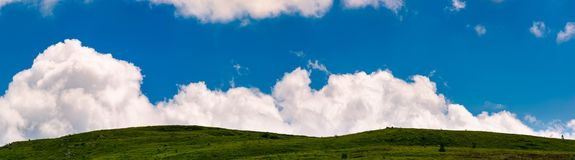 Cloud rising behind the grassy hills. Lovely panorama of cloudscape on a blue sky Royalty Free Stock Photography
