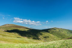 Cloud shadows on the green fields of spring mountains Stock Images