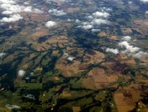 Cloud Shadows From The Top. 32,000 feet high, farm land below. Squares of grazing and planting areas Stock Photography