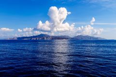 Cloud in shape of heart over the island in sea, Sunny summer weather, Greece, Aegean Royalty Free Stock Photo