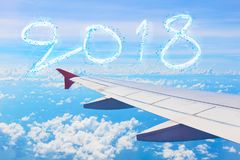 Cloud shape number 2018 years over wing airplane on the blue sky Royalty Free Stock Images