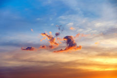 Cloud shaped like a dancing people. Cloud shaped like a dancing and jumping people. Colorful dramatic sunset with cloudy sky in Thailand. Bright afterglow Stock Photo